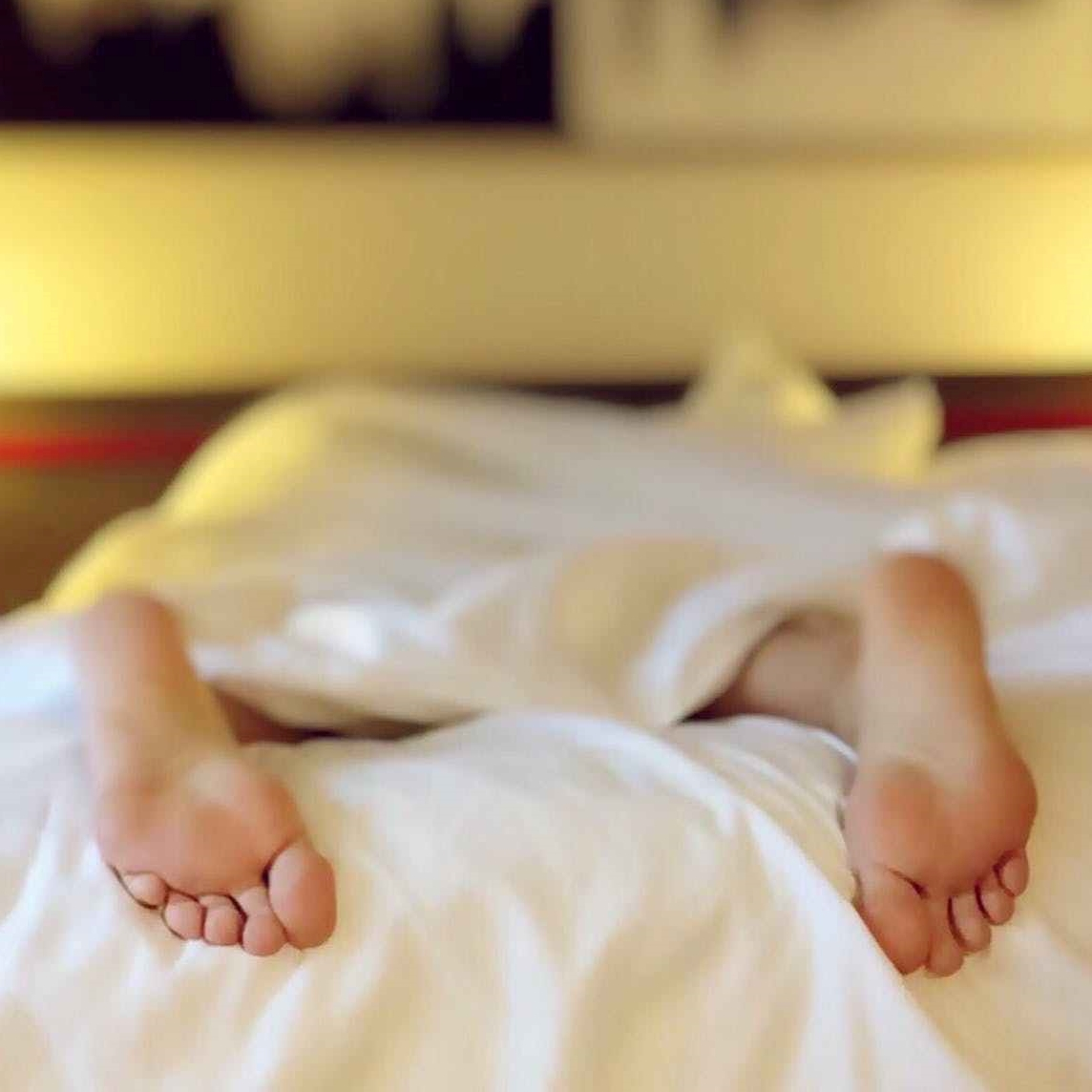 bare feet hang off a bed with white sheets