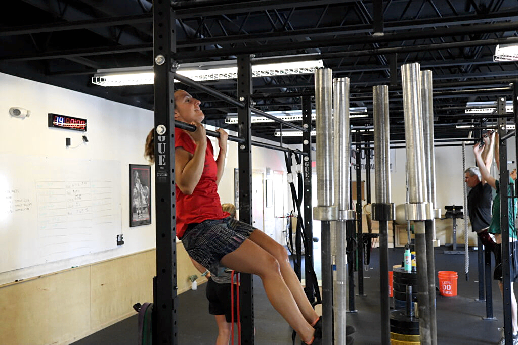 girl in red shirt and patterned shorts doing a pull up on black bars in a gym by a stack of barbells