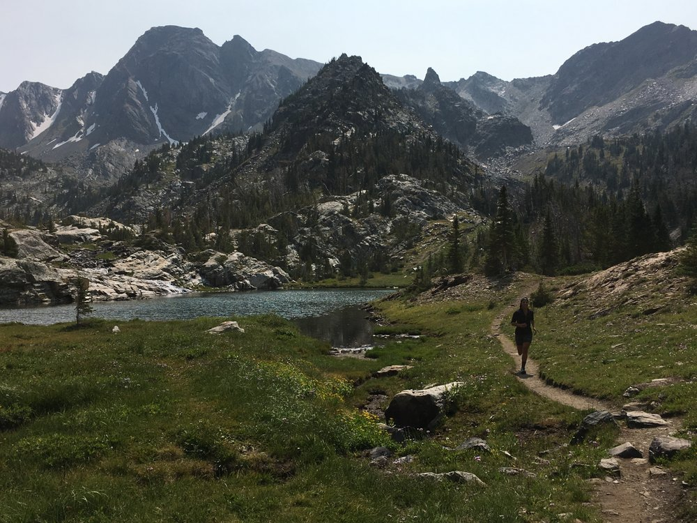 cliffs with snow and pine trees and rocks, an alpine lake, a narrow trail and a girl running on the trail