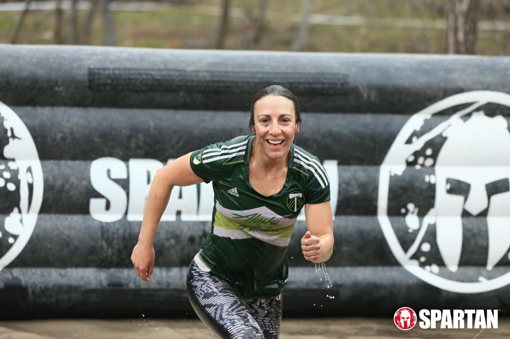 black wall with Spartan logo over a puddle in background, wet girl in green shirt and black pants running out of the puddle